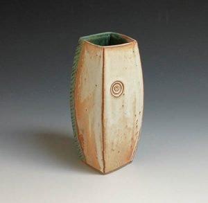 A tan and green handmade stoneware vase