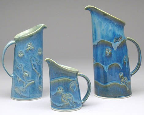 three different sized blue pitchers